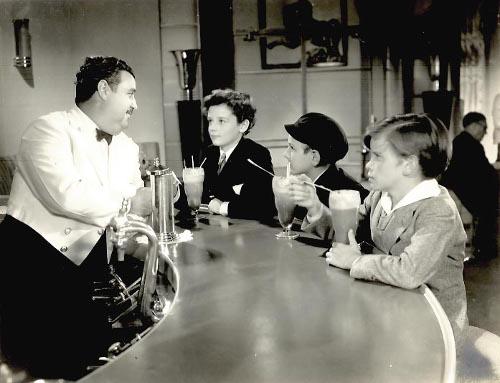 Vintage kids at soda fountain drinking egg cream.