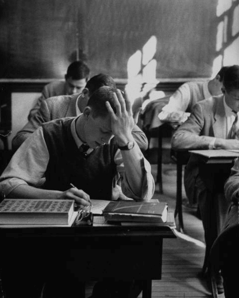 vintage young man taking exam in classroom head in hand