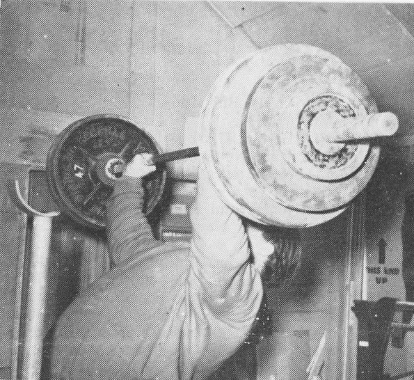 vintage man lifting barbell with heavy weights above head