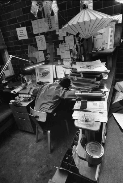vintage overworked mit student head down on desk piled high with papers