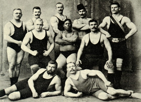 Vintage weightlifters strongmen posing flexing group photo.