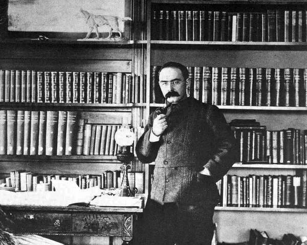 Rudyard Kipling smoking a pipe in library.