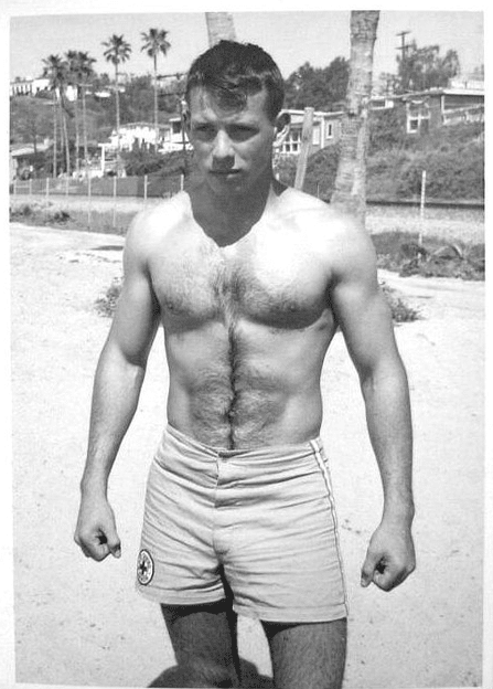 vintage man in swim trunks at beach strong physique