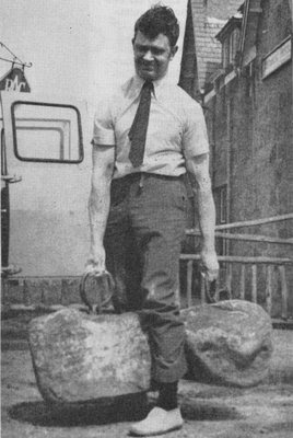 young man in business attire lifting heavy rocks