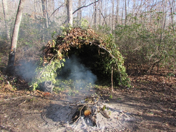 wigwam style survival shelter in woods with campfire