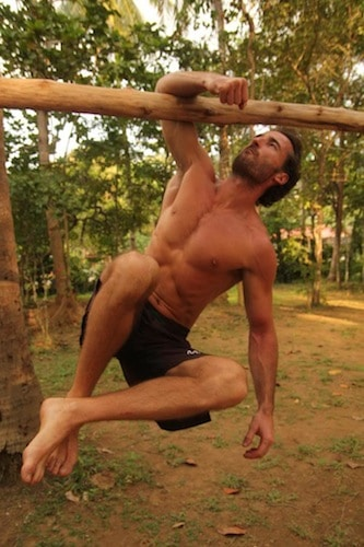 man hanging from branch one arm