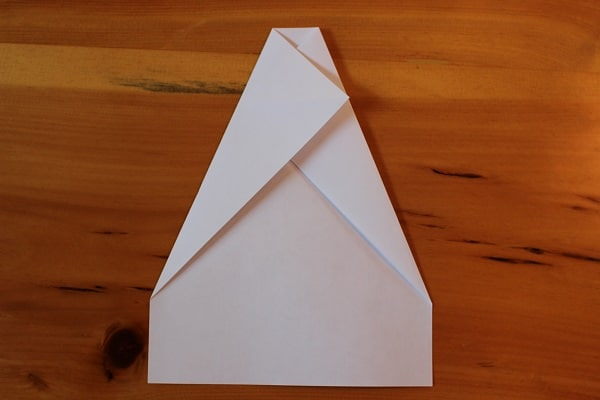 Fold top left corner down to meet diagonal crease in center.