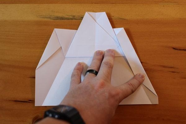 Fold corners in yet again to meet edge of top.
