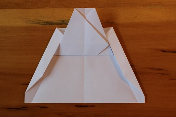 Both corners folded in — airplane almost done.