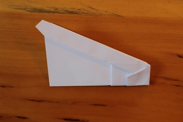 Fold airplane in half, outwards.