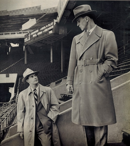 vintage college men 1948 in sports stadium wearing rain coats