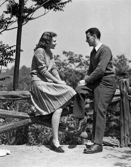 vintage couple sitting on fence post talking