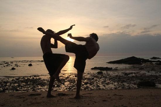 Two men training on beach at sunrise.