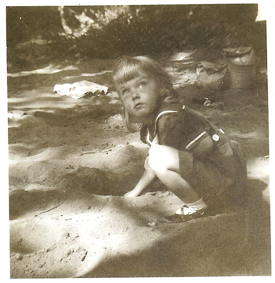 vintage little girl playing in dirt diggin hole