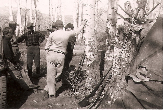 vintage hunters in woods talking rifles leaning on trees