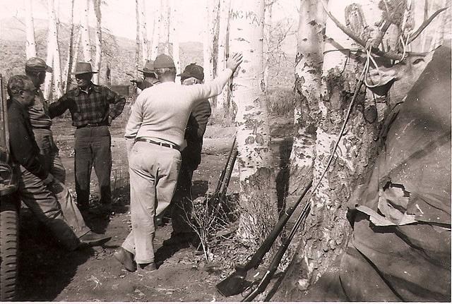 vintage hunters in woods talking rifles leaning on trees