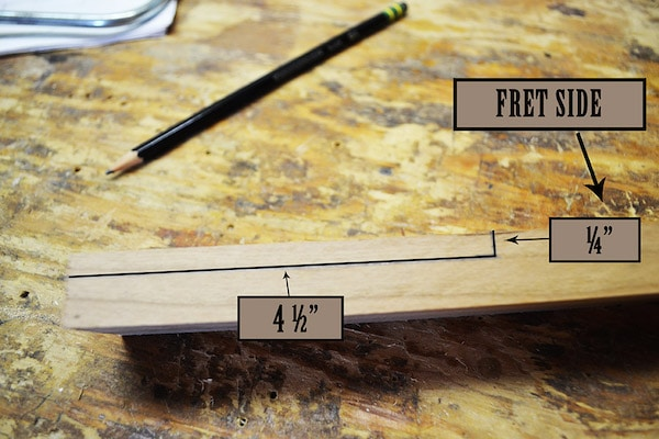Draw measurement line with pencil on wooden piece.