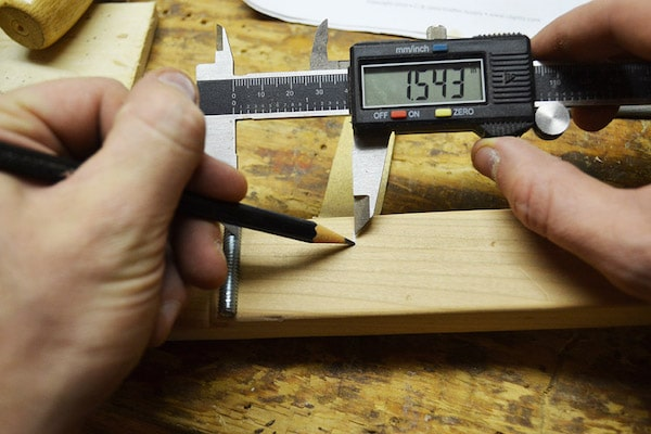 Man taking measurements by using digital vernier callipar on wooden block.