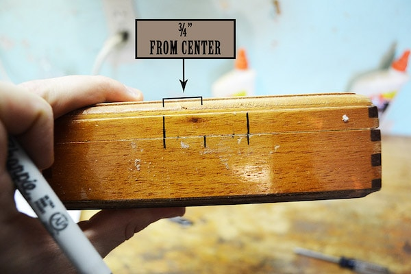 Man marking a central point of cigar box with marker.