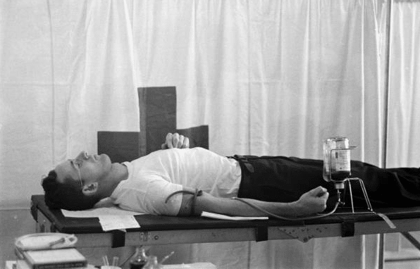 Vintage man laying on doctor table and donating blood.