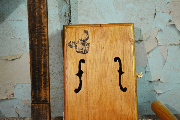 A man logo and f holes illustration on cigar box.