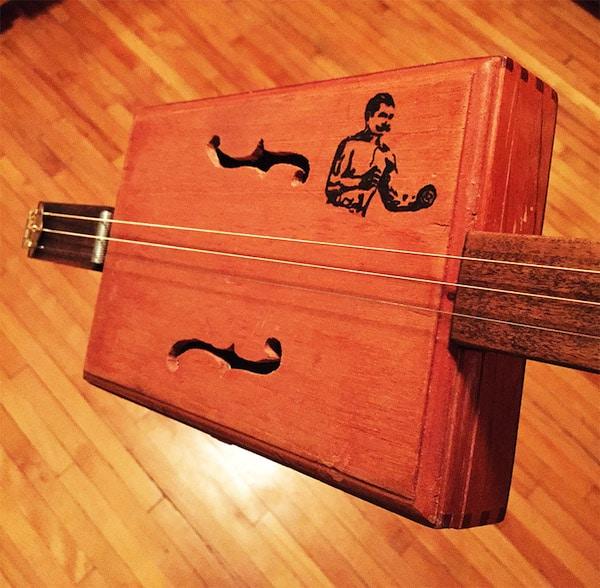 Man and f holes logo illustration on guitar body.