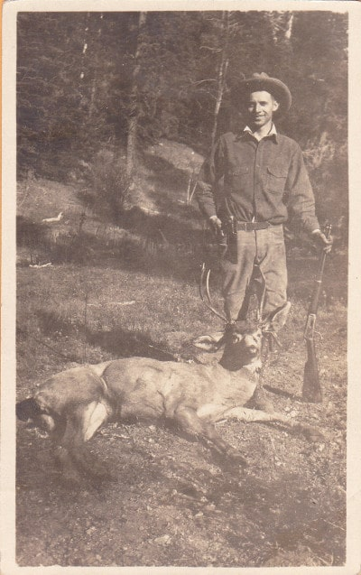 A hunter posing with deer in forest.