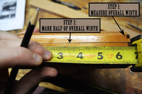 Man using pencil for take measurements of cigar box with inches footer.