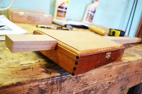 A wooden block is placed in the lid section of cigar box.