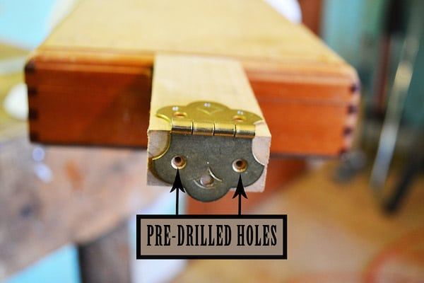Inserting the tailpiece of the guitar on cigar box.