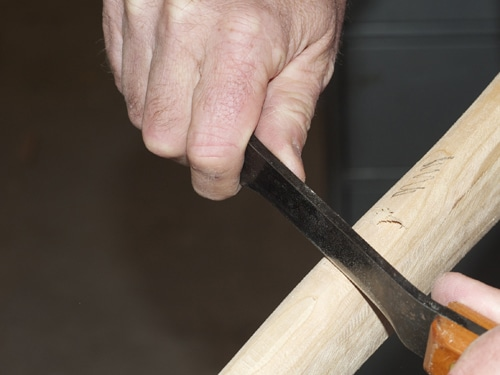 Men scraping wood handle with knife.