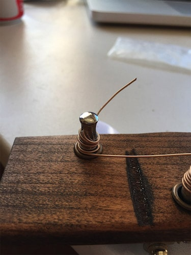 Attach two turners on cigar box with metallic wires.