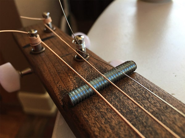 Straightening the turners wires of guitar with grooving nut.