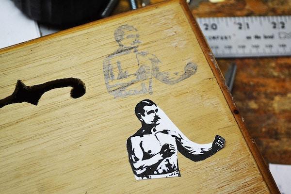A logo of strength man on cigar box.