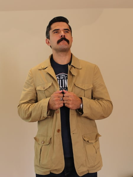 man posing in tan khaki travel jacket with a lot of pockets