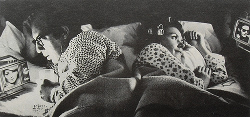 Couple lying on bed while watching tv.