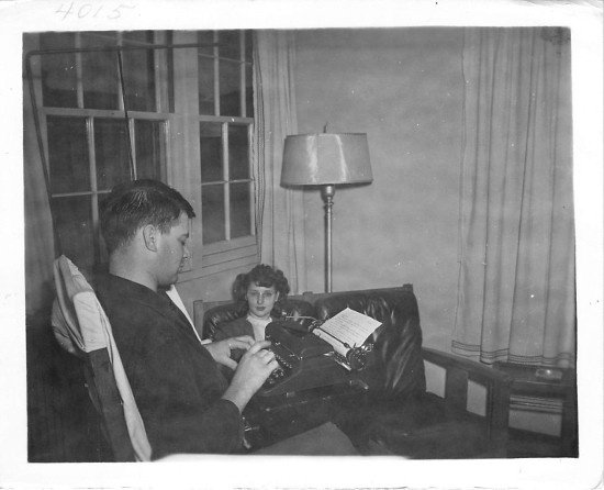 vintage man in living room writing on typewriter
