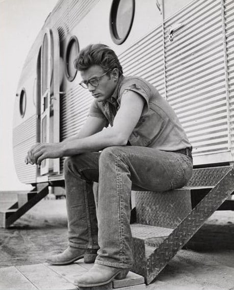 James Dean sitting outside camper wearing cowboy boots.
