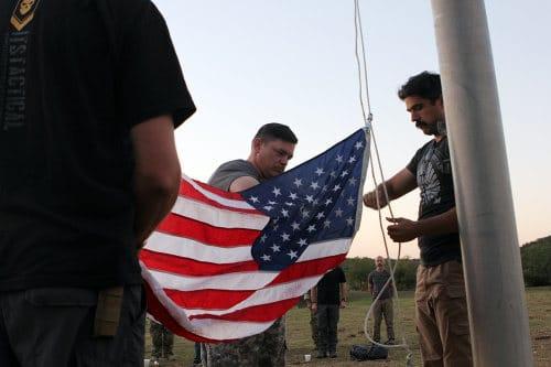 men at flagpole raising american flag