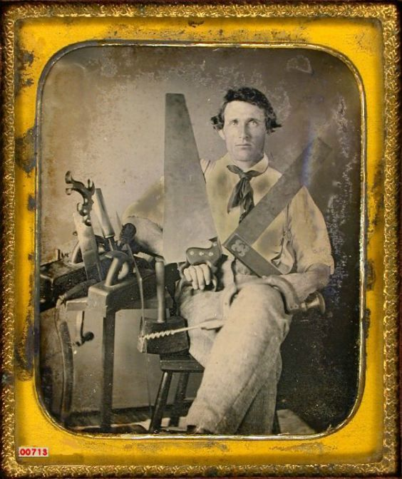 vintage man sitting portrait with saws hand tools