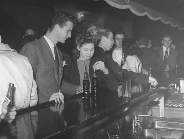 young couple having drink at crowded soda fountain