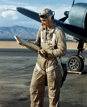 vintage pilot outside airplane looking at checklist