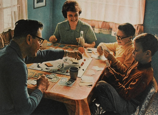 Vintage family playing board game at Table.