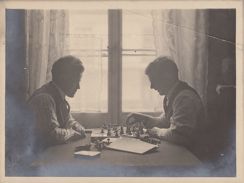 Vintge Men playing chess in front of window.