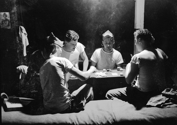 Vintage sailors playing poker in bunks.
