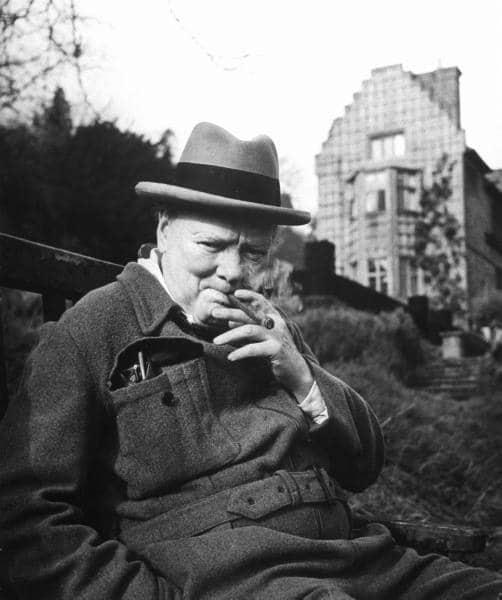 winston churchill sitting on bench smoking cigar