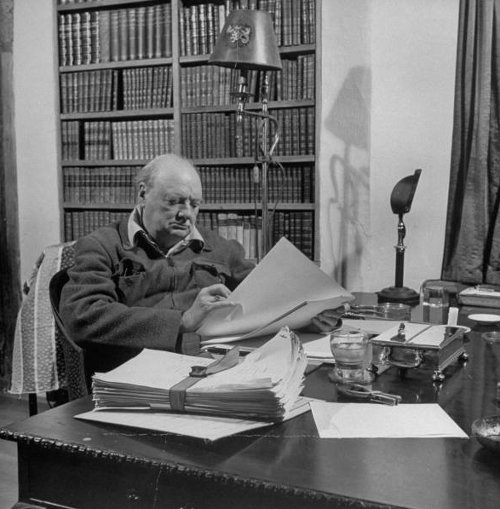 winston churchill sitting at desk in library reading