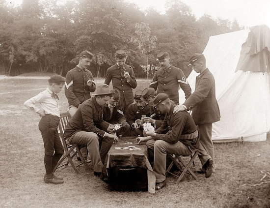 Soldiers in uniform playing cards in camp.