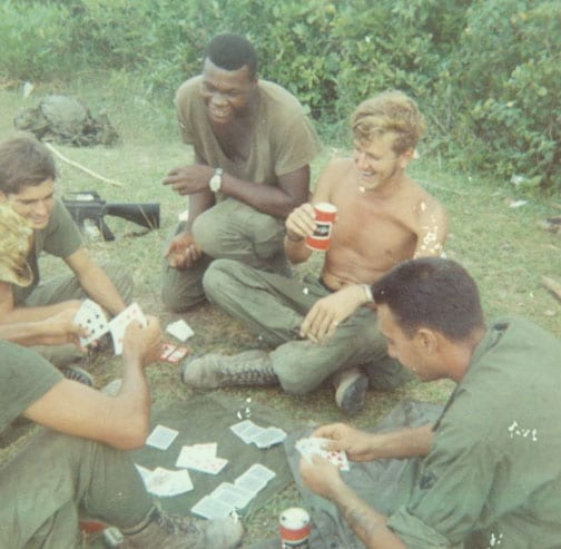 vintage vietnam soldiers playing cards in the grass