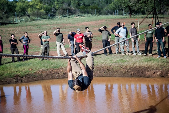 atomic athlete vanguard man hanging from rope over mud pit